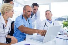 Doctor que muestra la PC del ordenador portátil a sus colegas Foto de archivo libre de regalías