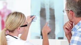 Doctor que muestra radiografías a su paciente metrajes