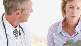 Doctor que muestra radiografías a su paciente almacen de metraje de vídeo