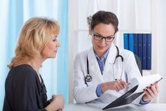 Doctor que muestra resultados de la prueba pacientes foto de archivo