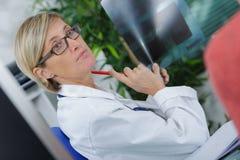 Doctor que muestra resultados de la radiografía al paciente imagen de archivo libre de regalías