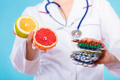 Doctor que ofrece las vitaminas químicas y naturales Imagen de archivo