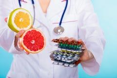 Doctor que ofrece las vitaminas químicas y naturales Fotografía de archivo libre de regalías