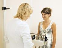 Doctor que pesa al paciente Imagenes de archivo