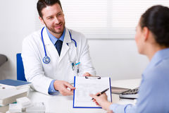 Doctor que pide que un paciente firme papeleo Fotografía de archivo
