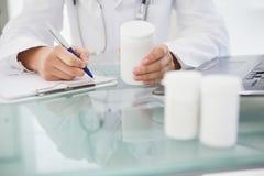 Doctor que pone prescripciones en escrito Fotos de archivo libres de regalías