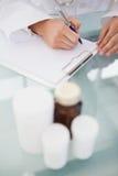 Doctor que pone prescripciones en escrito Foto de archivo