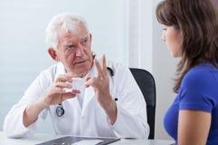 Doctor que prescribe píldoras rojas pacientes fotos de archivo libres de regalías