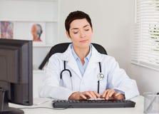 Doctor que pulsa con su ordenador Imagen de archivo libre de regalías