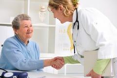 Doctor que sacude las manos al paciente fotografía de archivo