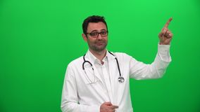 Doctor que señala el finger hasta esquina izquierda almacen de metraje de vídeo