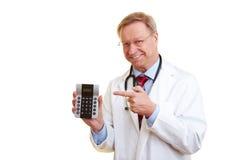 Doctor que señala a una calculadora Fotografía de archivo libre de regalías