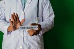 Doctor que se coloca en fondo verde Foco selectivo a disposición Alto texto del papel de Colesterol Concepto médico y de la atenc imagen de archivo libre de regalías