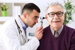 Doctor que sostiene el otoscopio y que examina el oído paciente foto de archivo libre de regalías