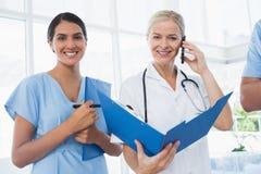 Doctor que sostiene la carpeta y que tiene llamada de teléfono imagen de archivo