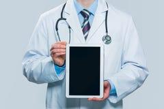 Doctor que sostiene la tablilla digital en blanco fotos de archivo