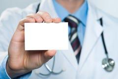 Doctor que sostiene la tarjeta de visita en blanco fotos de archivo