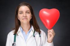 Doctor que sostiene un globo en forma de corazón Imágenes de archivo libres de regalías