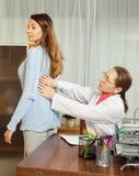 Doctor que toca detrás de paciente joven Imagen de archivo libre de regalías