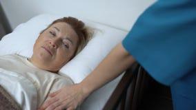 Doctor que toma la compresa de la frente mayor de los pacientes, mujer enferma favorable almacen de video