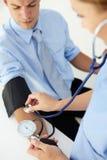 Doctor que toma la presión arterial del hombre joven Fotografía de archivo