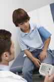 Doctor que toma la presión arterial del muchacho Imágenes de archivo libres de regalías