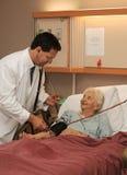 Doctor que toma la presión arterial mayor Imágenes de archivo libres de regalías