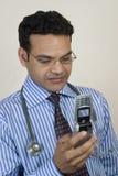 Doctor que toma llamada urgente Foto de archivo