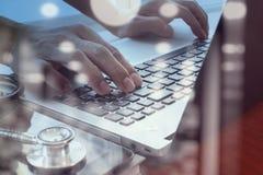 Doctor que trabaja con la tableta y el ordenador portátil digitales Foto de archivo