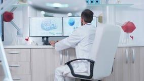 Doctor que trabaja en centro de investigación moderno con las exploraciones de cerebro 3D que muestran en monitores almacen de metraje de vídeo