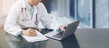 Doctor que trabaja en el escritorio con el ordenador portátil imágenes de archivo libres de regalías
