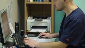 Doctor que trabaja en el ordenador almacen de metraje de vídeo