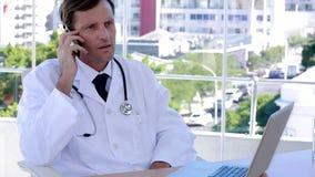 Doctor que trabaja en el teléfono y el ordenador portátil almacen de video