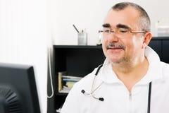 Doctor que trabaja en la PC Imagen de archivo libre de regalías