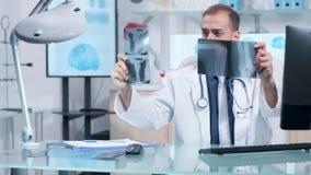 Doctor que trabaja en su oficina, analizando exploraciones de los rayos X almacen de metraje de vídeo