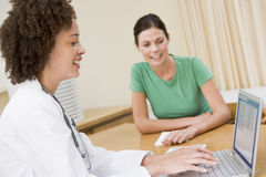 Doctor que usa la computadora portátil con la mujer en la oficina del doctor Imagenes de archivo