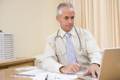 Doctor que usa la computadora portátil en la oficina del doctor Fotografía de archivo