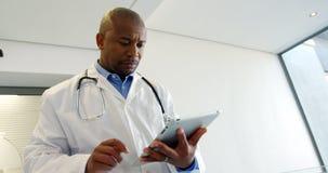 Doctor que usa la tableta digital mientras que camina en el pasillo