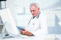 Doctor que usa la tableta digital por el ordenador fotos de archivo