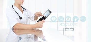 Doctor que usa la tableta en oficina e iconos médicos Foto de archivo