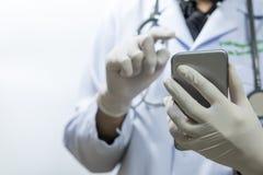 Doctor que usa smartphone con el paciente en la falta de definición interior del hospital para el fondo, búsqueda Imagen de archivo libre de regalías