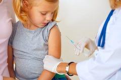 Doctor que vacuna al pequeño pelirrojo fotografía de archivo libre de regalías