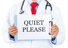 Doctor-quiet please. Closeup portrait of health care professional with red tie and stethoscope holding up sign which says quiet please, isolate on white royalty free stock images