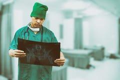 Doctor quirúrgico que mira la película de radiografía imagen de archivo libre de regalías