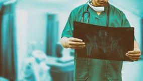 Doctor quirúrgico que mira la película de radiografía fotos de archivo