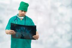 Doctor quirúrgico que mira la película de radiografía fotografía de archivo