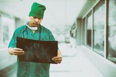 Doctor quirúrgico que mira la película de radiografía fotos de archivo libres de regalías