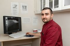 A doctor radiologist at the workplace looks at images from an X-ray machine on a computer monitor royalty free stock images