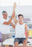 Doctor raising a young man arm Royalty Free Stock Image