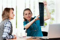 Doctor with x-ray. Medical doctor and patient analysing x-ray photography in hospital Stock Image